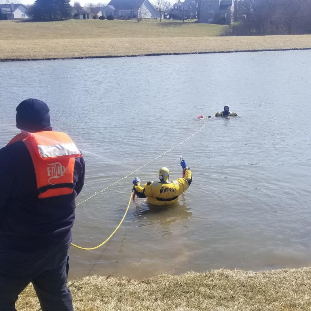 A member of the Fire Territory practices a water rescue in a retention pond